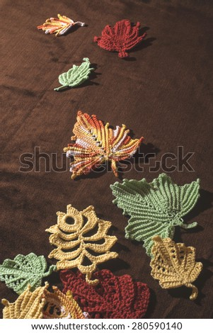 Knitted autumn leaves on brown textile - stock photo