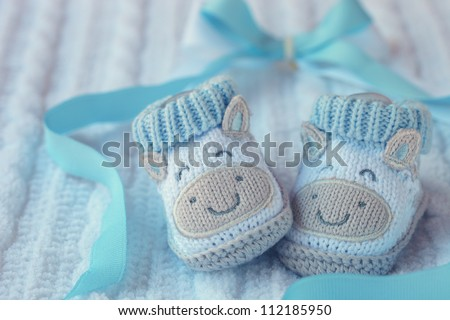 Knitted baby shoes for boy on a blue background. Greeting card. - stock photo