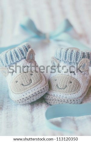 Knitted baby shoes for boy on a blue background. Greeting card baby shower, invitation, birthday. Vertical with copy space - stock photo
