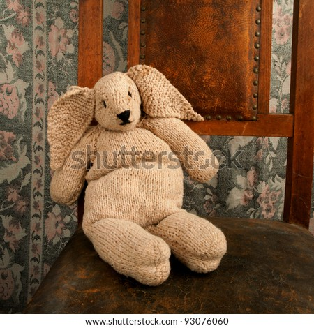 knitted bunny sitting on an old chair square - stock photo
