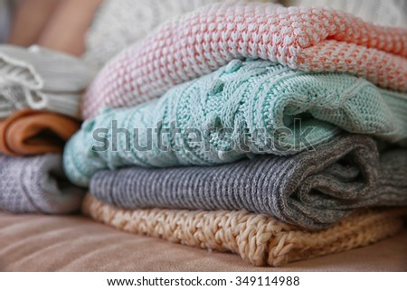 Knitted clothes on a sofa - stock photo