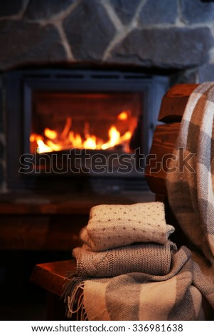 Knitted clothes on chair on fireplace background - stock photo