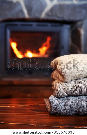 Knitted clothes on table on fireplace background