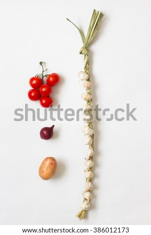 Knitted garlic, onion,  twig red tomatoes and potatoes on white