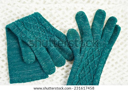 Knitted gloves in white scarf - stock photo