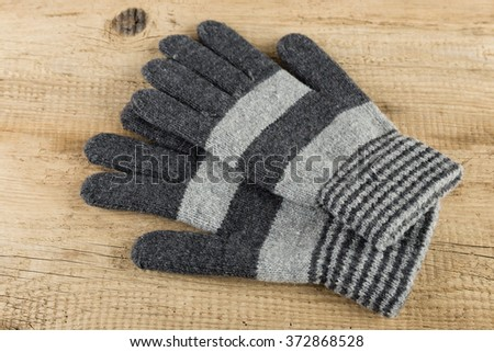 Knitted gloves on wooden background - stock photo