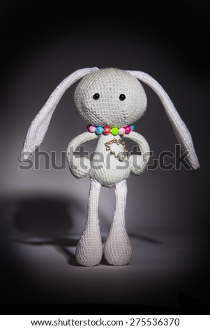 knitted gray rabbit with dimonds heart on the black gradient background - stock photo