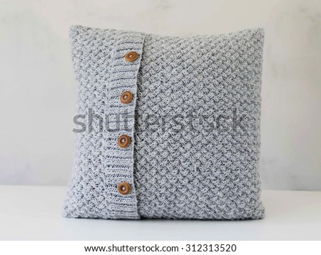 Knitted grey pillow with wooden buttons on white background