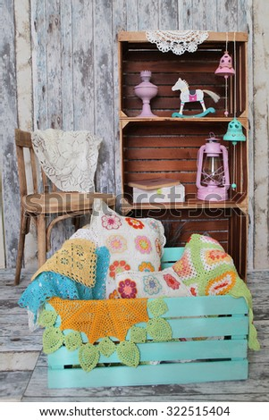 knitted home decorations in wooden box on retro interior background