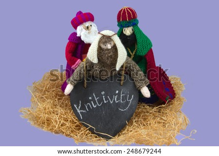 Knitted nativity figures holding a sign on heart slate saying Knitivity - stock photo