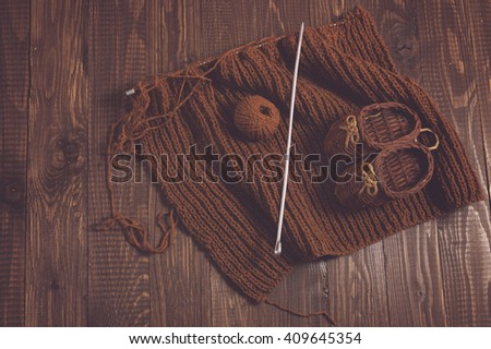 Knitted piece  and knitted kids shoes are on the table - stock photo