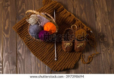 Knitted piece  and knitted kids shoes are on the table with a basket with clews of threads - stock photo