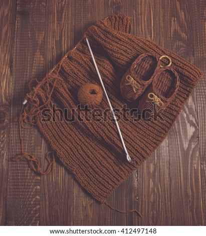 Knitted piece  and knitted kids shoes of brown thread are on the table - stock photo