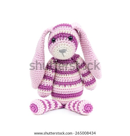 Knitted rabbit toy sitting over white background with soft shadow - stock photo