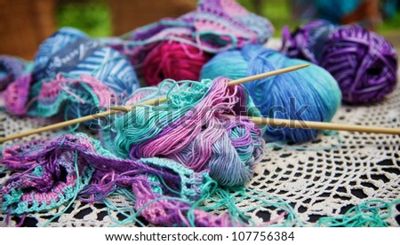 knitted wool and pin on a table - stock photo