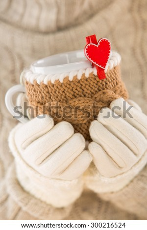 Knitted wool cup in human hands. With red hearts and the word love. - stock photo