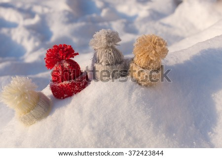 Knitted woolen hats on the snow. Winter concept / background - stock photo