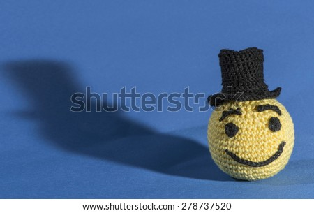 Knitted yellow emoticon with bowler on blue background - stock photo
