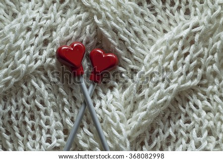 Knitting details, red hearts on white pattern - stock photo