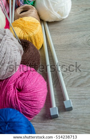 Knitting. Group of multicolor yarn and needles on grey wooden table. Close up. Copy space.