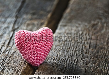 Knitting hearts on old wooden panel. Background Valentines Day.Valentines day cards. - stock photo