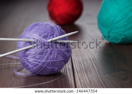 knitting needles and balls of threads on the wooden table - stock photo