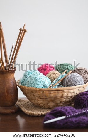 Knitting needles and yarn balls in basket - stock photo