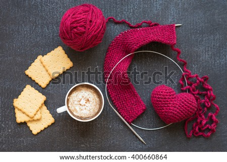 Knitting with red yarn and needles, heart, a cup of coffee and five crackers on dark grunge board