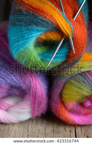 Knitting wool ball with needles on old wooden table - stock photo
