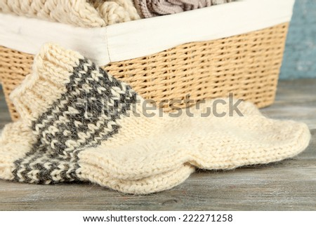 Knitting yarn in basket and socks, on wooden background