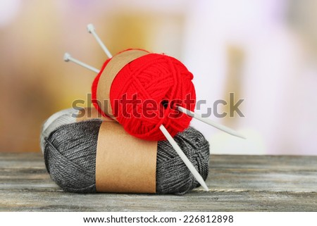 Knitting yarn with knitting needles on wooden table, on light background - stock photo