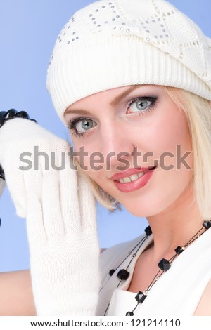 knitwear. woman wearing a winter cap and gloves on a blue  background