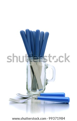 Knives in a mason jar glass with handle and a fork and spoon on the table top in front. Vertical format over white with reflection. - stock photo