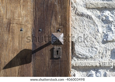knob and lock wrought iron on a wooden door - stock photo