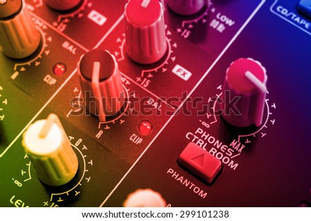 knobs board of a dj mixing console under colored disco lights - stock photo