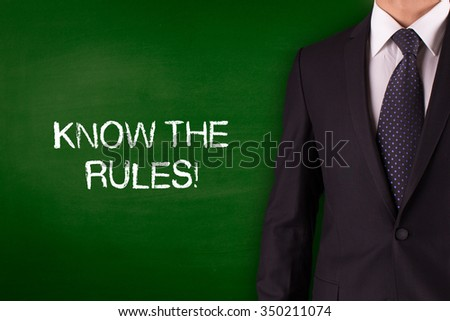 KNOW THE RULES! on Blackboard with businessman - stock photo