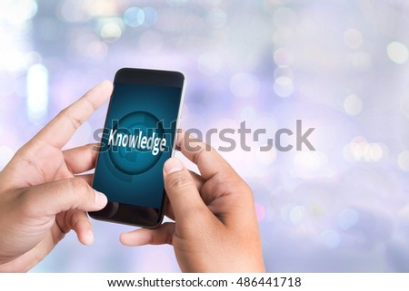 Knowledge   Expertise Intelligence Learn Knowledge person holding a smartphone on blurred cityscape background