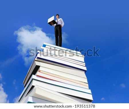 Knowledge is power - Happy business man using pc computer on a stack Of Books - stock photo