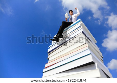 Knowledge is power - Happy business man using tablet pc computer and sitting on a stack Of Books - stock photo