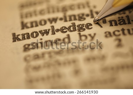 knowledge pen nib pointing to the words in the dictionary, shot with very shallow depth of field, - stock photo