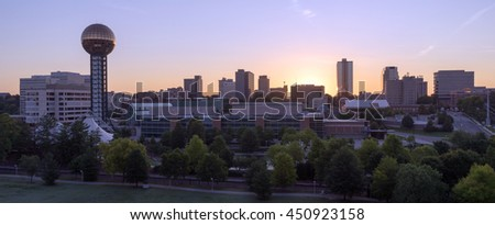Knoxville city skyline is backlit by the orange hues of sunrise - stock photo
