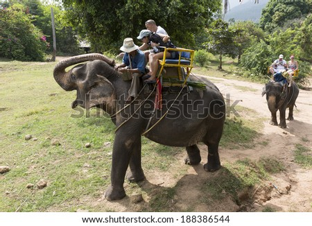 KO SAMUI, THAILAND -  December 27, Unidentified tourists riding elephant in Samui  jungle Thailand on December 27, 2013. Asian elephants are the largest living land animals in Asia. - stock photo