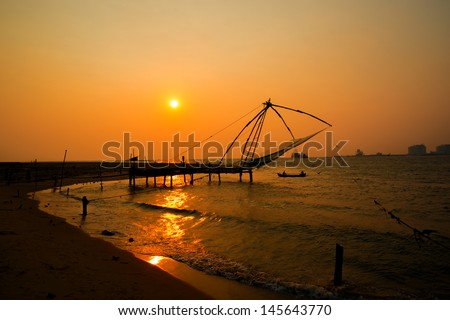 Kochi chinese fishnets and the boat with fishermen on sunset  in Kerala. Fort Kochin, Kochi,  South India - stock photo