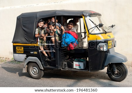KOCHI, INDIA - FEBRUARY 25: Unidentified school children in uniform going home after classes at primary school by a rickshaw on February 25, 2013. India, Cochin (Kochi),  Kerala - stock photo