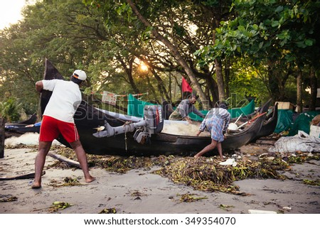 Kochi, India - November 29, 2015: Indian fishermen after fishing in their wooden boats in the early morning on the sea beach in Fort Kochi (Cochin), Kerala, India.