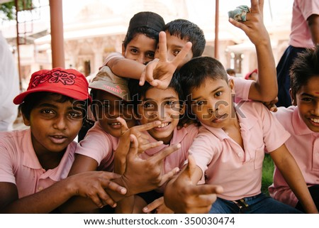 Kochi, India - November 28, 2015: Playful Indian children having rest and smiling on the street after school in Fort Kochi (Cochin), Kerala, India. - stock photo