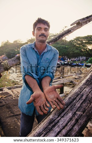 Kochi, India - November 29, 2015: Traditional technology of fishing. Fisherman shows damaged hands after hard working on Chinese fishing net on the sea beach in Fort Kochi (Cochin), Kerala, India.
