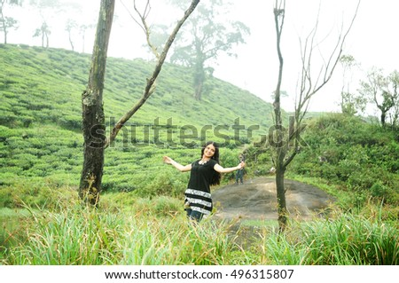 KODAIKANAL, INDIA - JUNE  30TH, 2015: A girl raised her hands. Happiness and freedom in mountains