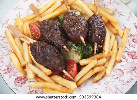 Kofta kebab, turkish minced meat skewer with salad and french fries