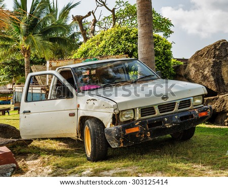 KOH CHANG, THAILAND- APRIL 17, 2015: Old car produced by the Japanese company Nissan, standing on the beach with an open door
